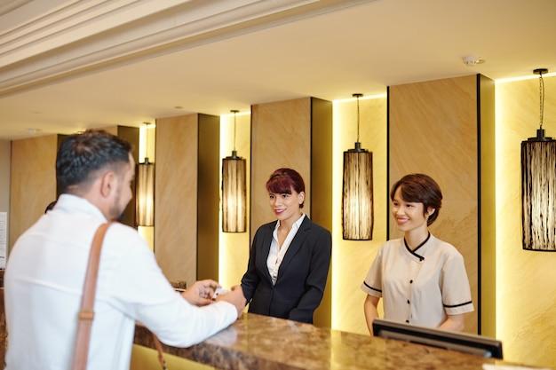 ゲストと話し、部屋を選ぶのを手伝ってくれるかわいいアジアのホテルの受付マネージャーの笑顔