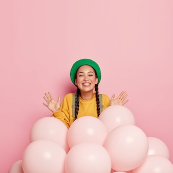 미소 짓는 예쁜 아시아 여성은 헬륨 풍선 근처에서 손바닥을 들어 올리며 기분이 좋으며 녹색 베레모와 노란색 캐주얼 점퍼를 입고 특별 행사를위한 공간을 장식합니다.