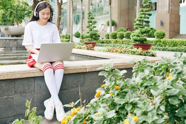 噴水のそばに座ってノートパソコンで作業しているかわいいアジアの女子高生の笑顔