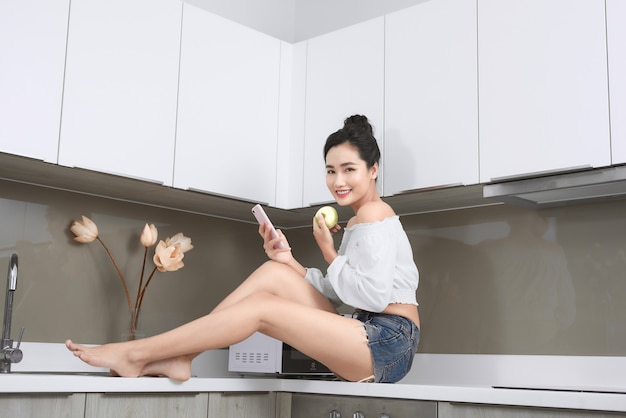 携帯電話を見て、台所でリンゴを持って笑顔のかなりアジアの女性。