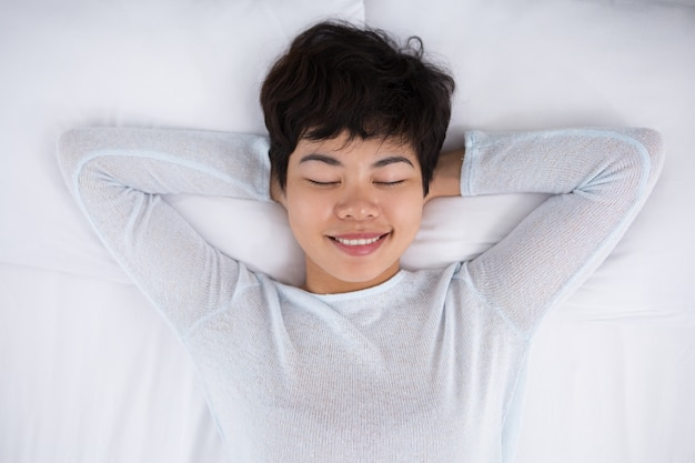 Smiling pretty asian woman sleeping in bed