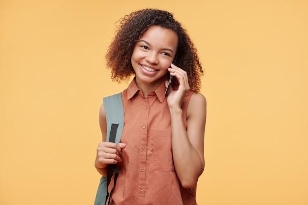 かばんを持って、黄色の背景に対して携帯電話で話している巻き毛のかわいい黒人女子高生の笑顔