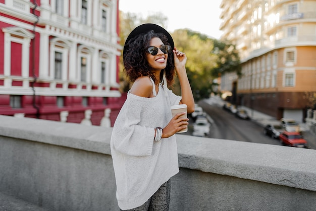Smiling pretty black woman in white sweater and black hat holding cup of coffee.