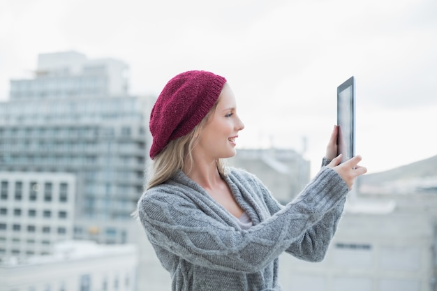Smiling pretty blonde holding tablet outdoors