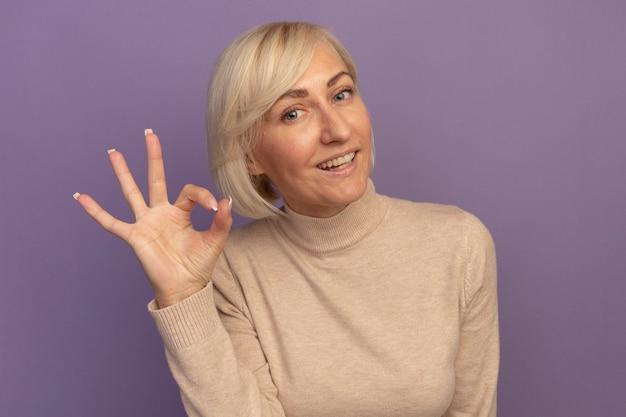 笑顔のきれいな金髪のスラブ女性のジェスチャーok紫の手サイン