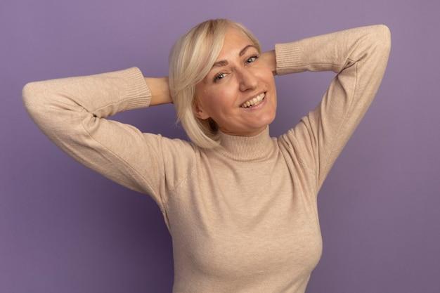 笑顔のきれいな金髪のスラブ女性は紫の後ろに頭を抱え