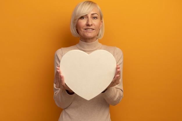 La donna slava abbastanza bionda sorridente tiene la forma del cuore isolata sulla parete arancione