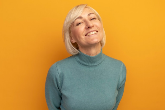 Улыбающаяся красивая белокурая славянская женщина смотрит на перед, изолированную на оранжевой стене
