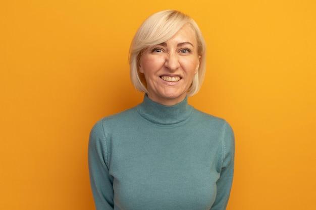 오렌지 벽에 고립 된 전면에 보이는 웃는 예쁜 금발 슬라브 여자