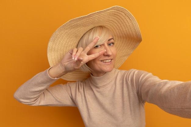 Sorridente bella bionda donna slava con cappello da spiaggia gesti il segno della mano di vittoria che finge di tenere la fotocamera sull'arancio