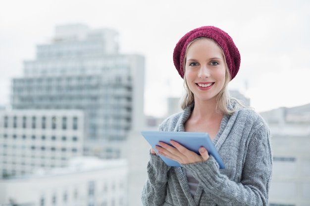 Smiling pretty blonde using tablet pc outdoors