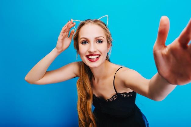Улыбаясь симпатичная блондинка с голубыми глазами позирует, принимая селфи, наслаждаясь вечеринкой. носить черное платье и повязку на голову с кошачьими ушками.