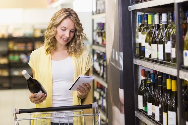 Улыбается довольно блондинка женщина с бутылкой вина в руке и, глядя на блокнот
