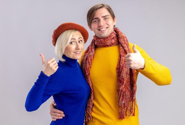 Sorridente bella donna bionda con berretto e bell'uomo slavo con sciarpa intorno al collo pollice in alto isolato sul muro bianco con copia spazio