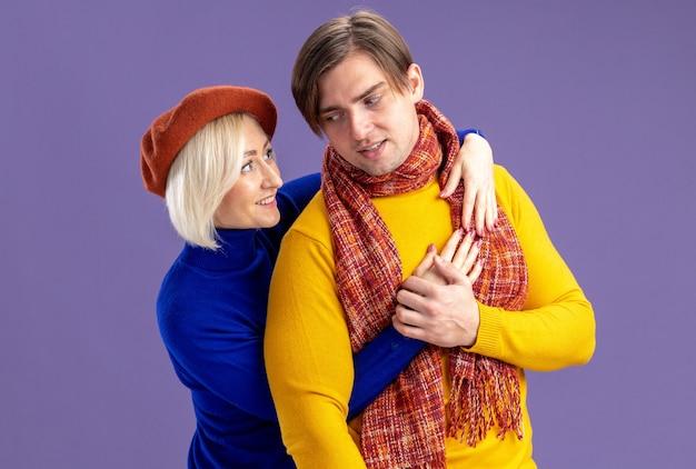 Sorridente bella donna bionda con berretto che abbraccia e guarda un bell'uomo slavo con una sciarpa intorno al collo