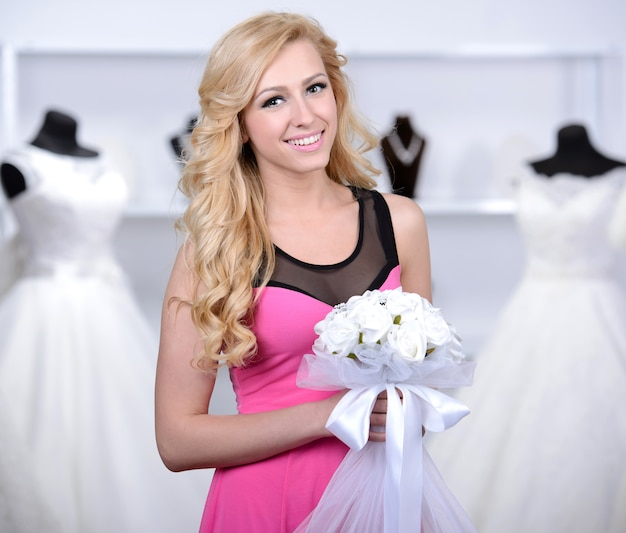 Smiling pretty bride chooses white gown at shop.