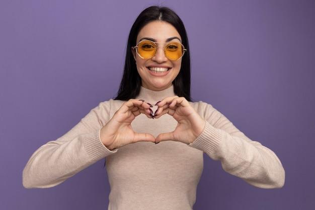 サングラスでかなりブルネットの白人の女の子の笑顔は紫のハートの手サインをジェスチャーします