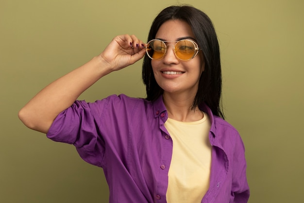 태양 안경에 웃는 예쁜 갈색 머리 백인 여자는 올리브 그린에 측면에서 보이는