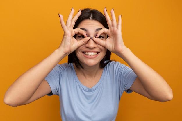 La ragazza caucasica del brunette grazioso sorridente esamina la macchina fotografica tramite le dita sull'arancio Foto Gratuite