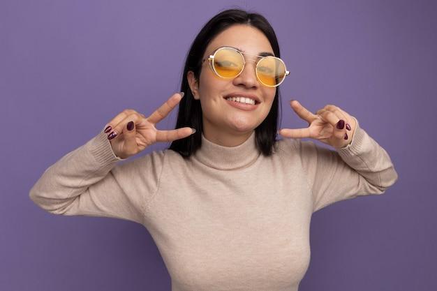 Sorridente ragazza caucasica abbastanza mora in occhiali da sole gesti il segno della mano di vittoria con due mani sulla porpora