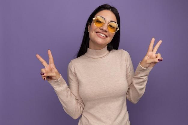 Sorridente ragazza caucasica abbastanza mora in occhiali da sole gesticolano segno di mano di vittoria con due mani sulla porpora