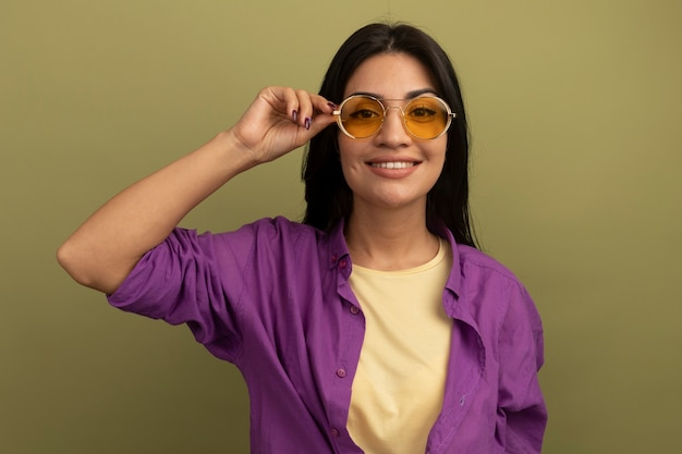 La ragazza caucasica abbastanza mora sorridente in occhiali da sole esamina la macchina fotografica su verde oliva Foto Gratuite