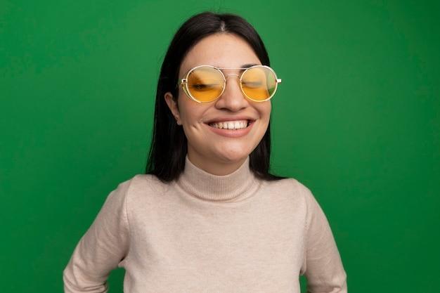 La ragazza caucasica abbastanza mora sorridente in occhiali da sole sta con gli occhi chiusi sul verde