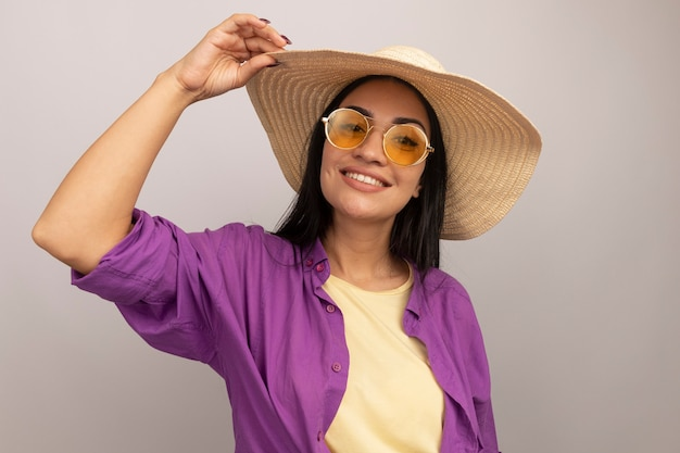 La ragazza caucasica abbastanza mora sorridente in occhiali da sole con il cappello della spiaggia mette la mano sul cappello su bianco