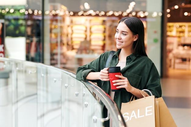 手すりに立って、ショッピングモールのホールで魔法瓶カップから熱いお茶を飲むかわいいブルネットの女の子の笑顔