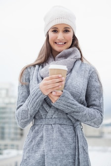 Smiling pretty brunette with winter clothes on holding coffee