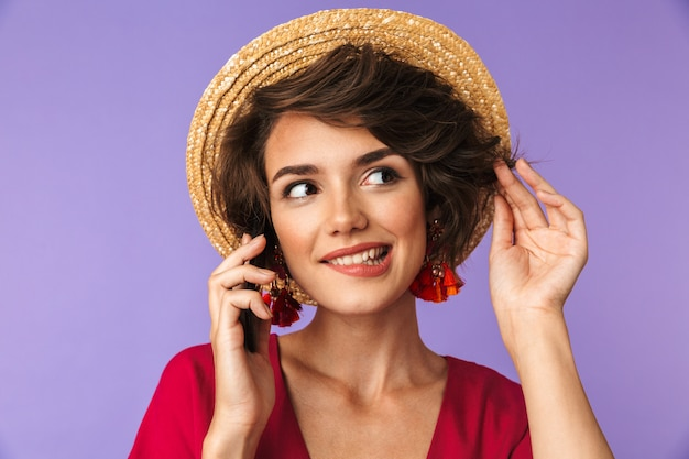 Smiling pretty brunette woman in dress and straw hat