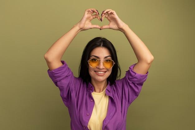 Улыбается красивая брюнетка женщина в солнцезащитных очках жесты сердца знак рукой над головой, изолированные на оливково-зеленой стене