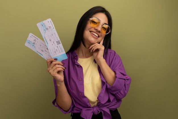 サングラスでかなりブルネットの女性の笑顔は顔に手を置き、オリーブグリーンの壁に分離された航空券を保持します。