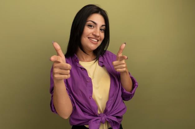 Улыбающаяся симпатичная брюнетка женщина указывает вперед двумя руками, изолированными на оливково-зеленой стене