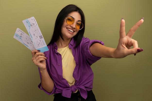 Sorridente bella donna castana in occhiali da sole gesti il segno della mano di vittoria e tiene i biglietti aerei isolati sulla parete verde oliva