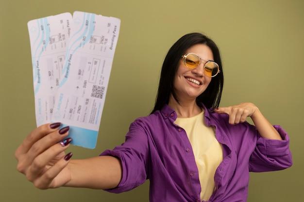 La donna graziosa sorridente del brunette in occhiali da sole tiene ed esamina i biglietti aerei isolati sulla parete verde oliva