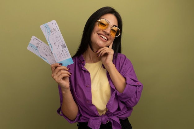 Sorridente bella donna mora in occhiali da sole mette la mano sul viso e tiene i biglietti aerei isolati sulla parete verde oliva