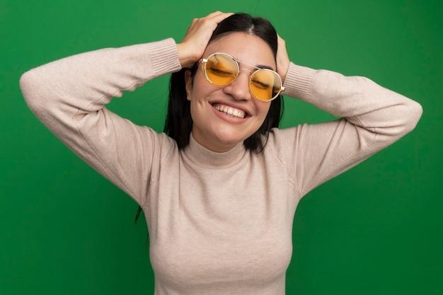 Sorridente bella donna castana in occhiali da sole mette le mani sulla testa isolata sulla parete verde