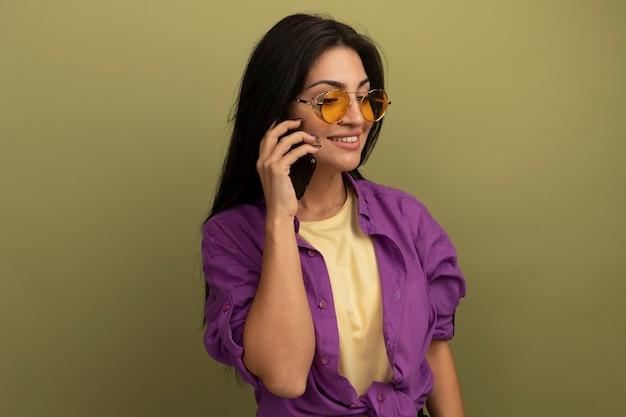 Sorridente bella donna castana in colloqui di occhiali da sole sul telefono isolato sulla parete verde oliva
