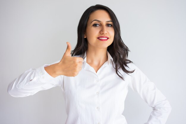 Smiling pretty business woman showing thumb up
