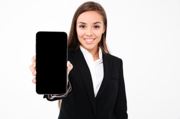 携帯電話のディスプレイを示すかなりの実業家の笑みを浮かべてください。
