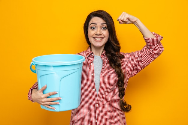 Sorridente bella donna caucasica più pulita che tiene in mano il secchio e tende i bicipiti?