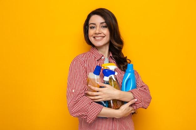 Sorridente donna più pulita caucasica che tiene in mano spray e liquidi per la pulizia