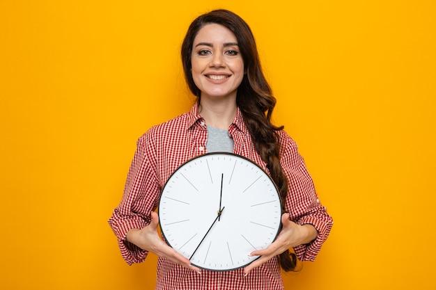 Sorridente donna più pulita caucasica che tiene l'orologio e guarda?
