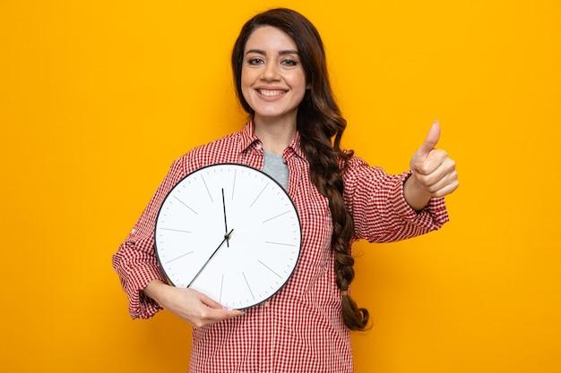Sorridente donna delle pulizie piuttosto caucasica che tiene l'orologio e fa il pollice in su