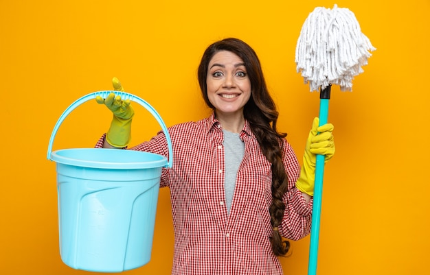 Smiling pretty caucasian cleaner woman with rubber gloves holding bucket and mop