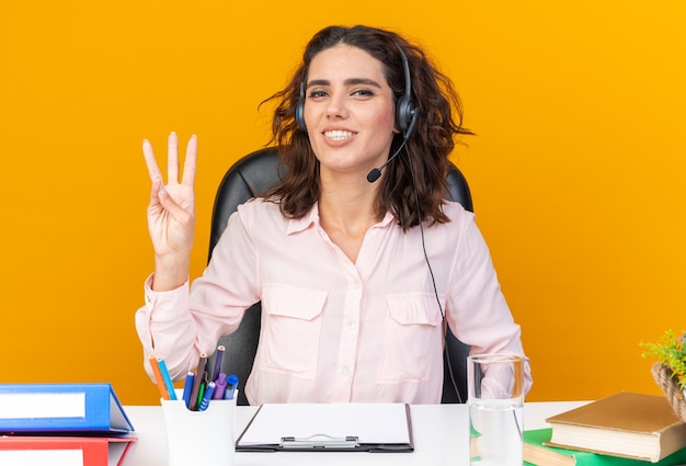 Smiling pretty caucasian female call center operator on headphones sitting at desk with office tools gesturing three with fingers