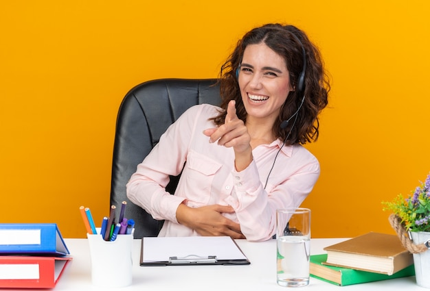 Smiling pretty caucasian female call center operator on headphones sitting at desk with office tools pointing at front