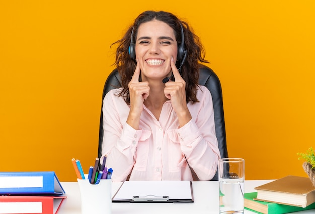 Smiling pretty caucasian female call center operator on headphones sitting at desk with office tools putting fingers on her face