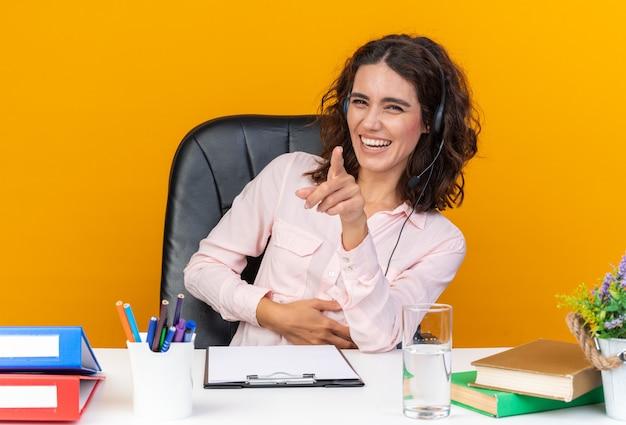 Улыбающийся довольно кавказский оператор колл-центра в наушниках сидит за столом с офисными инструментами, указывая вперед